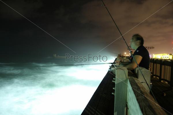 Рыбак на причале ночью