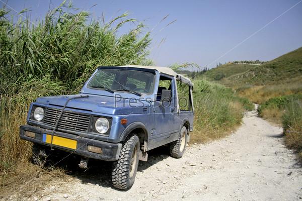 Старый синий грузовик стоит на пыльной дороге