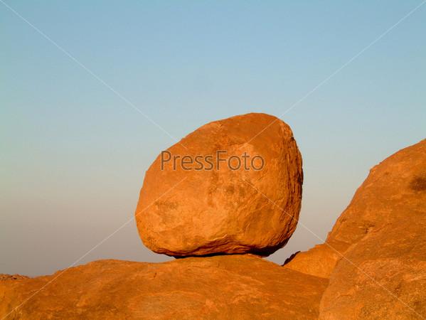 Огромный гранитный валун, расположенный на скалах, на фоне голубого неба