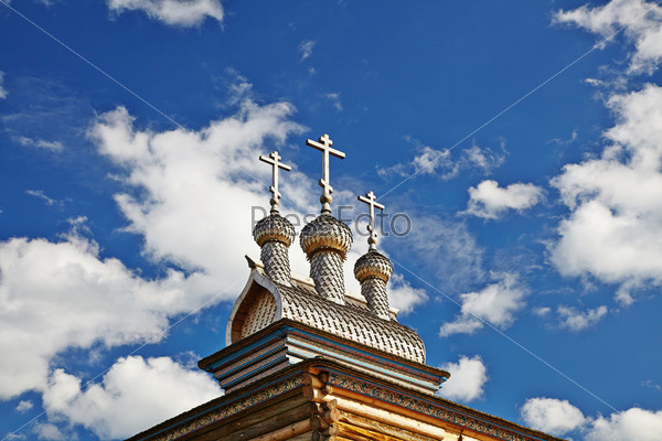 Фотография на тему Деревянные купола православной церкви с крестами в солнечный летний день.  Синее небо как фон