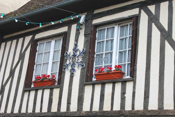 Праздничные рождественские украшения на фасаде старого французского дома