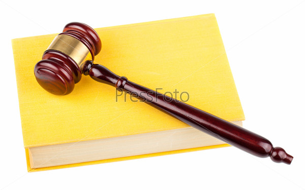 Деревянный молоток на желтой книге