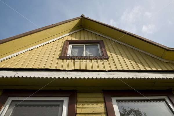Фронтон загородного дома с окнами и коньком