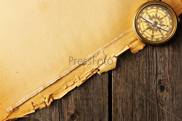 Старый латунный компас на старом фоне