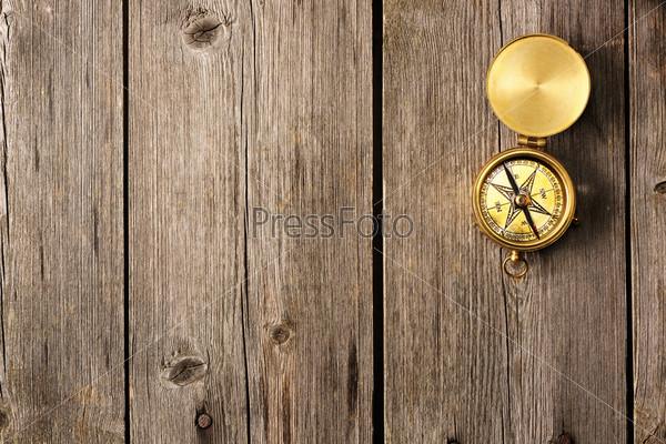Антикварный компас на деревянном фоне