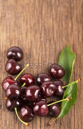 Красная спелая сочная вишня на деревянных досках