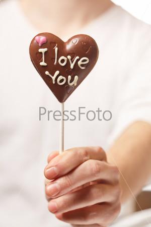 Человек с шоколадным сердцем в руке