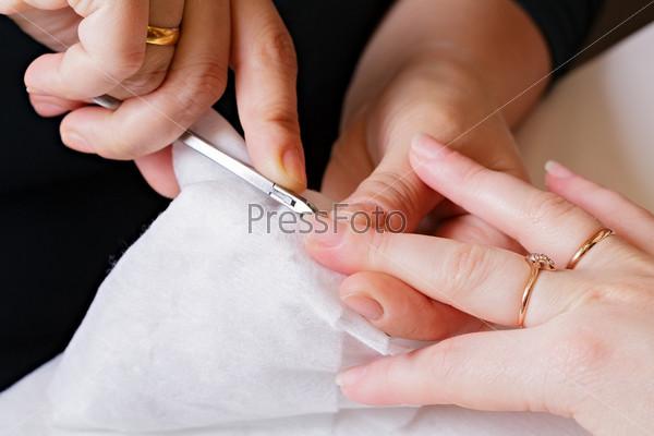 Мастер маникюра отрабатывает женские ногти, крупный план