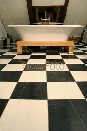 Ванна на черно-белом кафельном полу