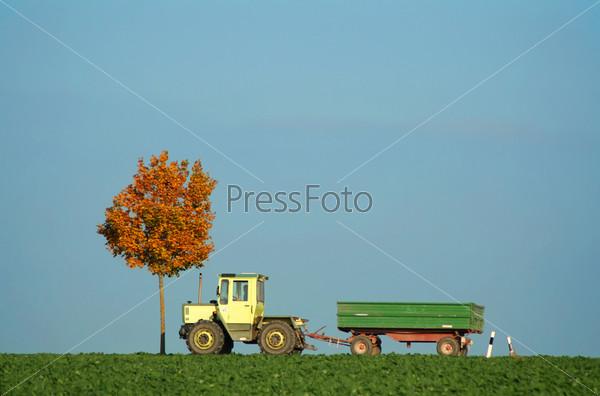 Трактор едет по осеннему полю