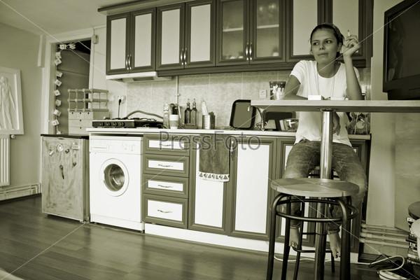 Молодая женщина сидит и курит за стойкой на кухне