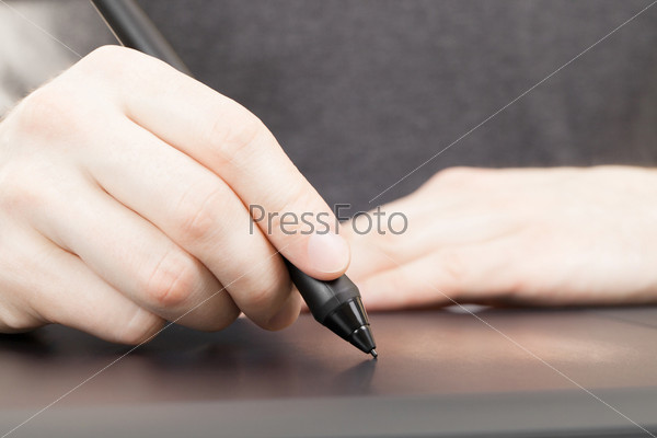Человек пишет пером на профессиональном графическом планшете