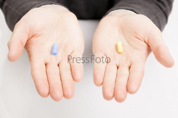 Мужчина держит по одной таблетке на каждой ладони