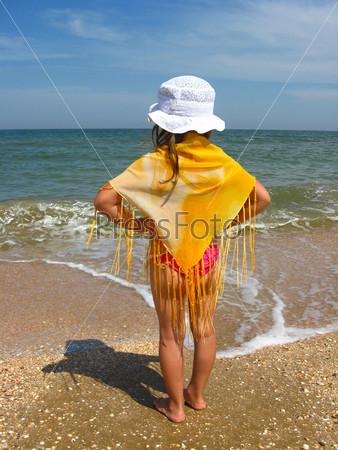 Девочка стоит на берегу моря