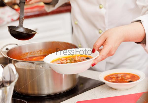 Шеф-повар готовит солянку в кухне