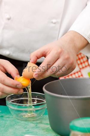 Повар разбивает яйцо в тарелку