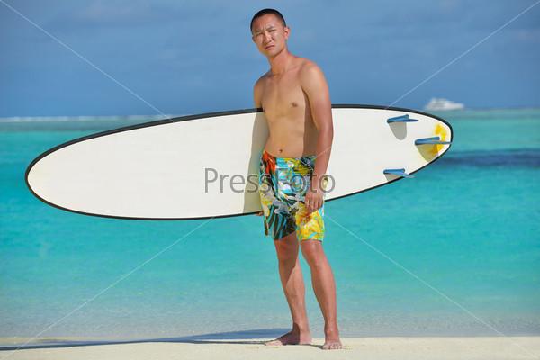 Счастливый молодой человек наслаждается летом на пляже