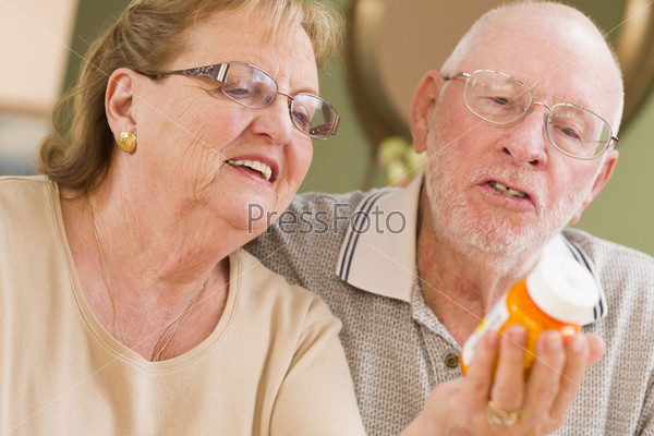 Пожилая пара читает надпись на бутыльке лекарства