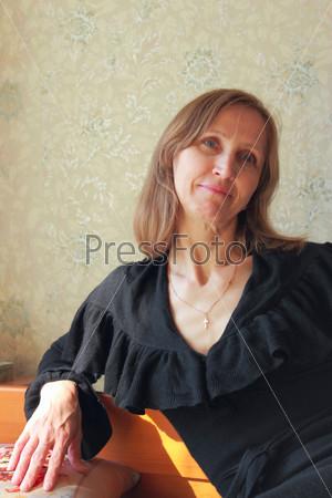 Фотография на тему Женщина в черном платье сидит на кровати