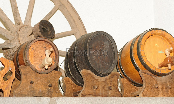 Деревянное колесо телеги и антикварные деревянные пивные бочонки