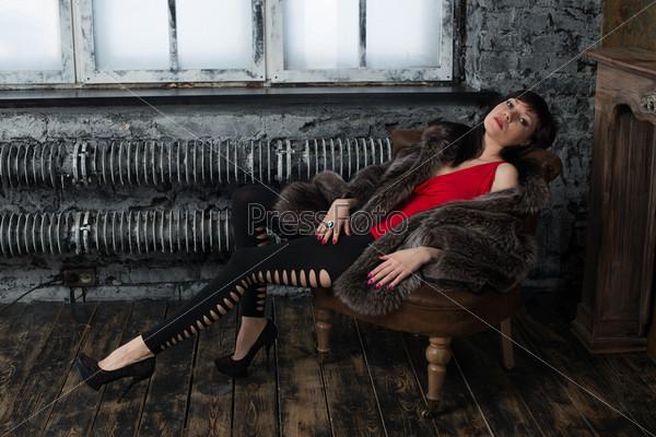 Очаровательная женщина в шубе отдыхает в старинной комнате