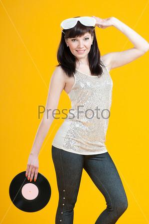 Улыбающаяся девушка позирует с виниловой пластинкой на желтом фоне