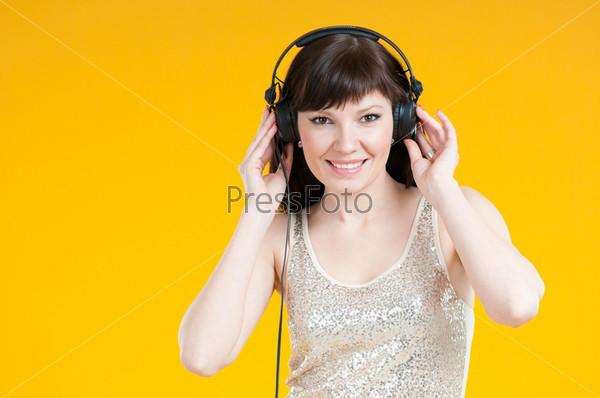 Фотография на тему Счастливая женщина, слушающая музыку в наушниках, студийная съемка