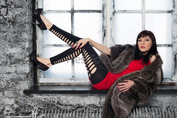 Модная молодая женщина позирует на подоконнике