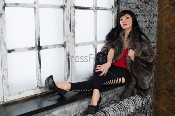 Фотография на тему Модная молодая женщина позирует на подоконнике