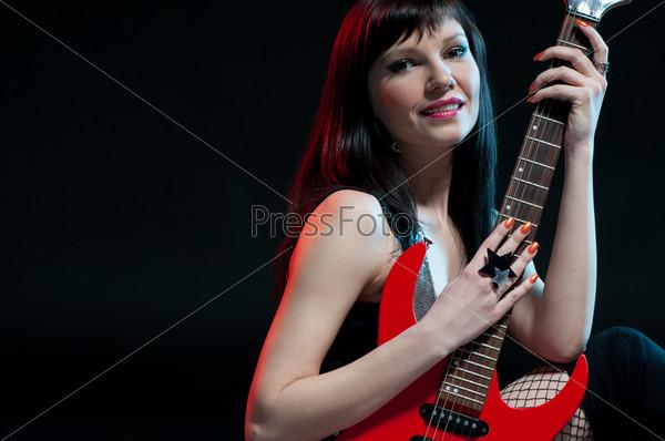 Улыбающаяся женщина позирует с электрической гитарой, темный фон