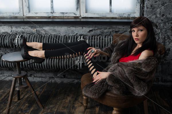 Модная молодая женщина позирует в винтажном интерьере