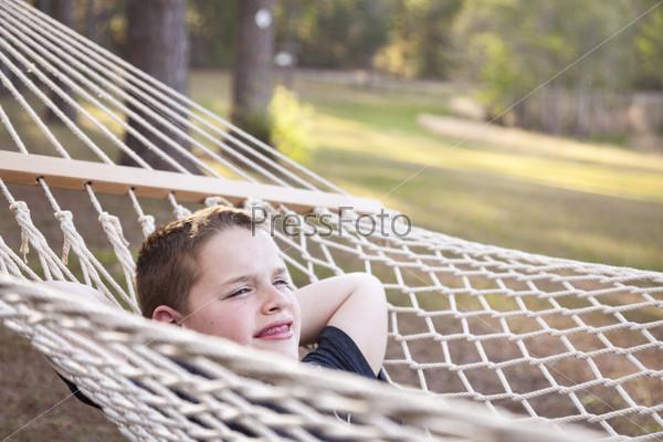Мальчик наслаждается днем в гамаке