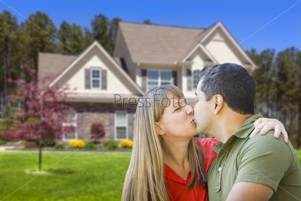 Пара смешанной расы обнимается перед домом