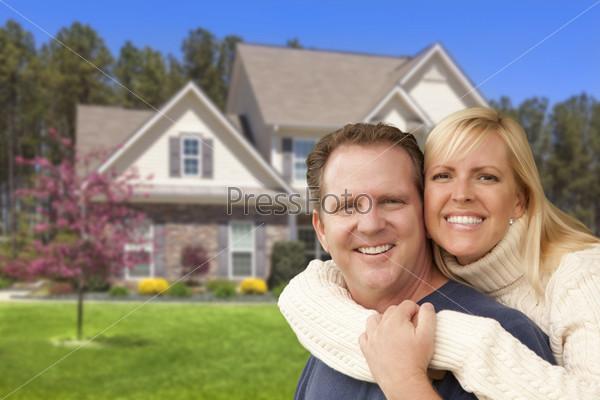 Счастливая пара обнимается перед домом