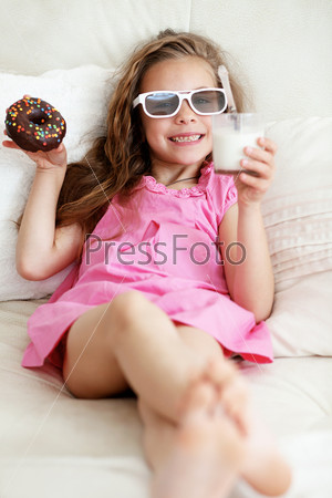 Девочка ест на диване