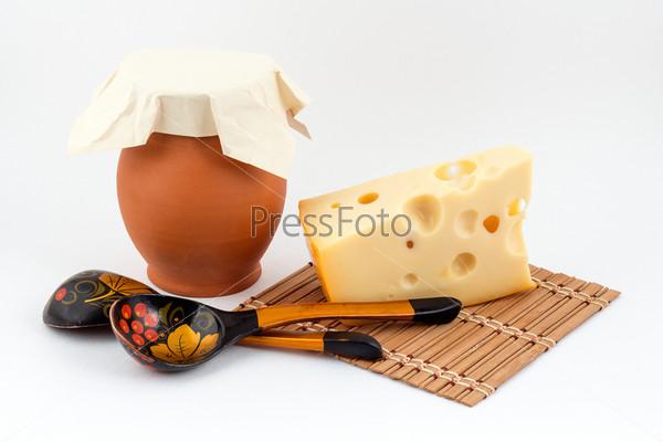 Фотография на тему Кусок сыра с кувшином и деревянными ложками на белом фоне