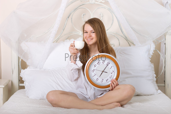 Фотография на тему Молодая красивая женщина в постели с будильником