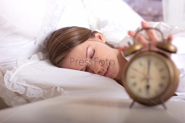 Девушка спит и отключает будильник
