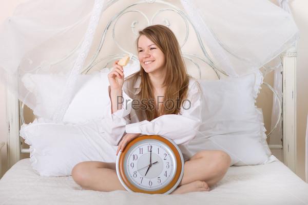 Молодая красивая женщина в постели с будильником