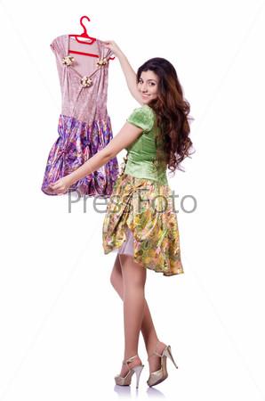 Женщина пытается выбрать платье на белом фоне