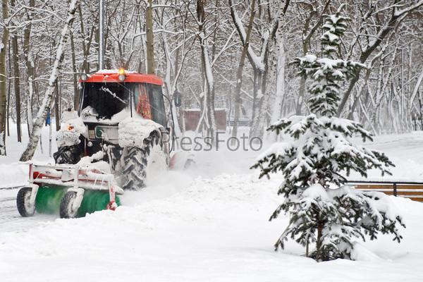 Небольшой трактор убирает снег