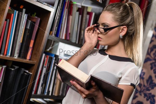 Студентка в библиотеке с книгой