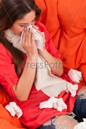 Молодая женщина с простудой сидит дома