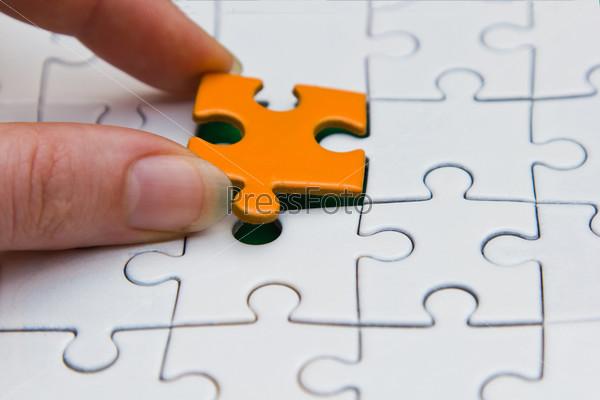 Рука, размещающая кусок головоломки