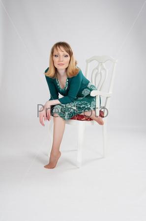 Фотография на тему Женщина в зеленом платье сидит на стуле
