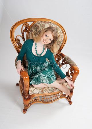 Женщина в зеленом платье сидит на стуле