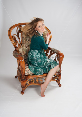 Женщина в зеленом платье, сидящая на стуле