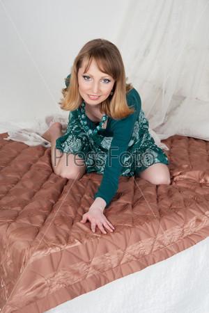 Сексуальная женщина в зеленом платье на кровати