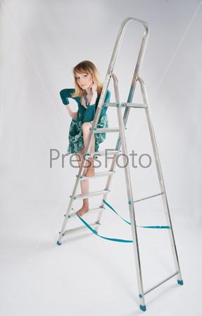 Женщина в зеленом платье стоит на стремянке