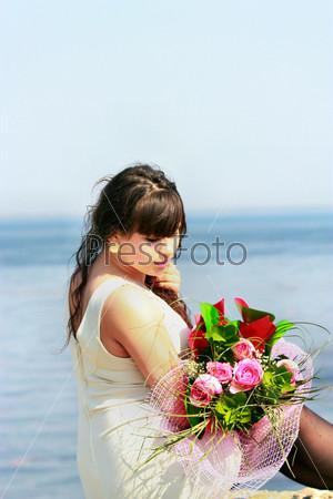 Молодая брюнетка с букетом роз